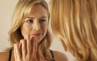 A middle age woman looking in the mirror at herself